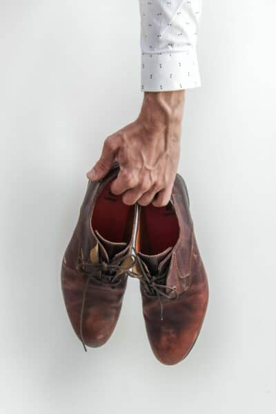 elderly person holding shoes