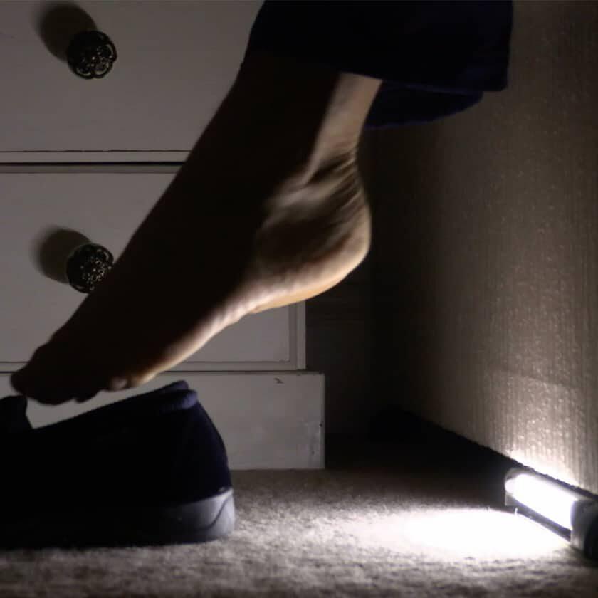 motion sensor night light illuminating floor under person's foot - fall prevention